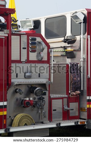 Detail of portion of fire truck showing hoses and tools. - stock photo