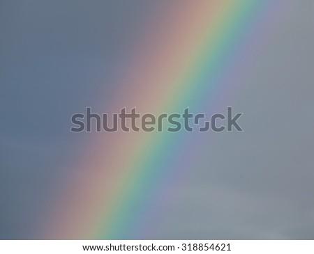 Detail of rainbow against dark cloud, showing full colour spectrum. - stock photo
