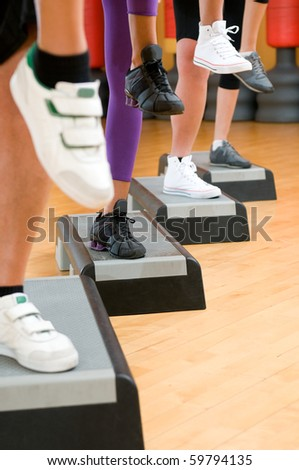 Detail of raised feet during aerobic step exercise at gym