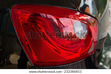 Detail of rear red lighthouse black car with reflections  - stock photo