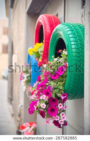 Detail of red and green tires recycled as planters with environmentally friendly method. - stock photo