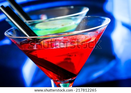 detail of red cocktail on blue blur background, dance disco concept - stock photo