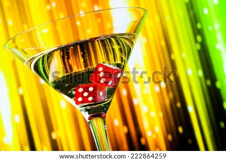 detail of red dice in the cocktail glass on colorful gradient background - stock photo