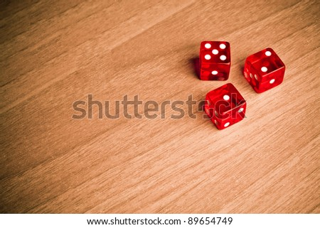 detail of red dice on old wood with space for text - stock photo