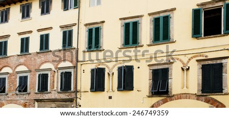 Detail of residential buildings with green window shutters in the town of Lucca, Tuscany, Italy.   - stock photo