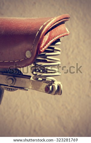 Detail of retro bike saddle. Suspension mechanism have two springs. Vintage style. Vertical image.