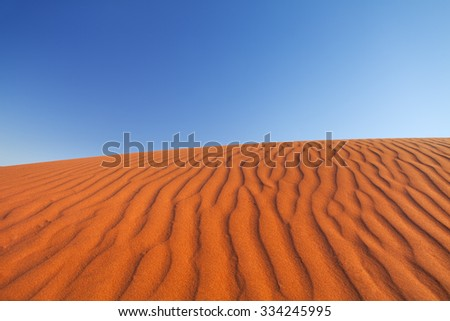 Detail of ripples in a red sand dune on a clear day. Photographed in the Northern Territory in Australia. - stock photo