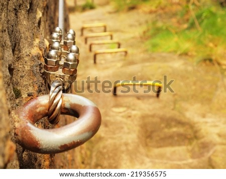 Detail of rope end anchored into sandstone rock.  Iron twisted rope fixed in block by screws snap hooks.  - stock photo