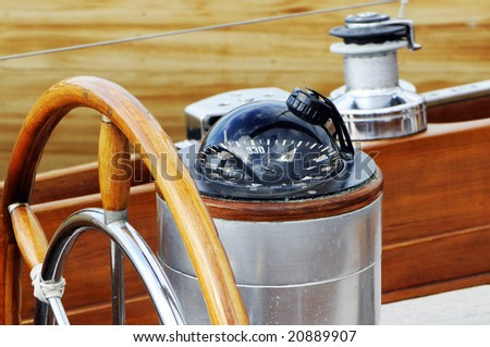 Detail of rudder and compass on a wooden sailboat - stock photo
