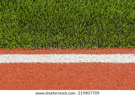 Detail of running track rubber lanes with the artificial grass. - stock photo