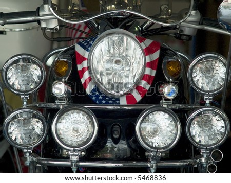 Detail of scooter with the pattern of the American flag wrapped around the headlight and lots of extra lights. - stock photo