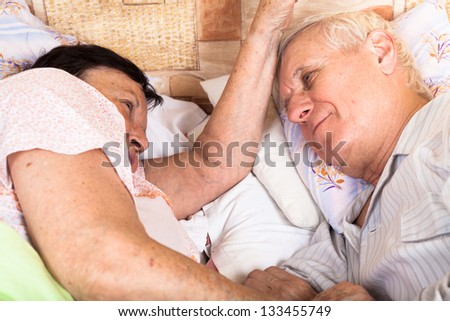 Detail of senior couple relaxing in bed. - stock photo