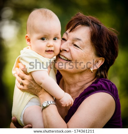 Detail of senior woman holding her granddaughter outdoor in nature - stock photo