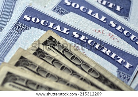 Detail of several Social Security Cards and cash money symbolizing retirement pensions financial safety - stock photo
