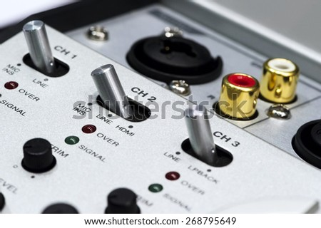Detail of silver DJ mixer controller with buttons, switches, faders, knobs, other toggle items, plugs and connectors, selective focus  - stock photo