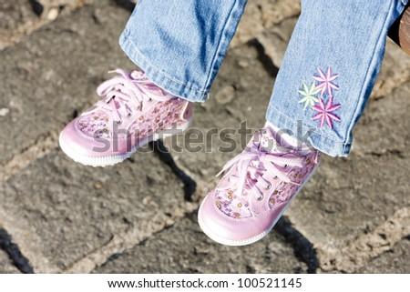 detail of sitting girl wearing pink shoes - stock photo