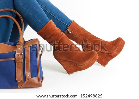 detail of sitting woman wearing fashionable platform brown shoes with a handbag - stock photo