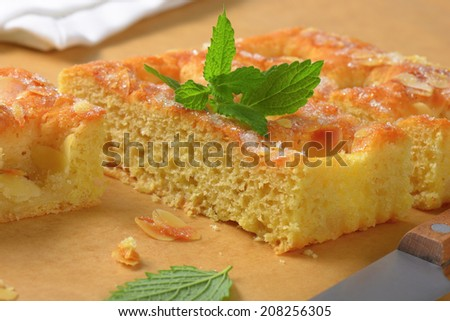 detail of sliced sponge cake with almond flakes and mint on baking paper
