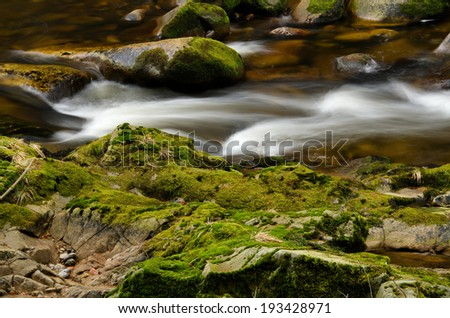 Detail of small cascade on mossy stone. - stock photo