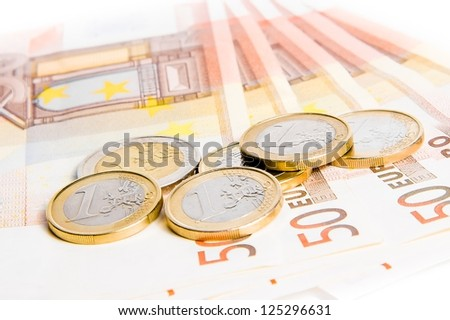 detail of some euro coins on 50-euro banknotes on white background - stock photo