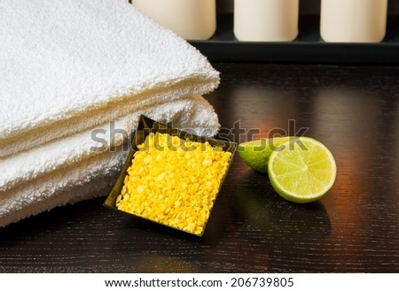 detail of spa massage border background with towel stacked white candles sea salt and lime on wood table - stock photo