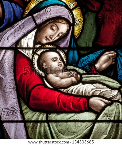 Detail of stained glass window depicting Christmas scene, the infant Jesus with Mary - stock photo