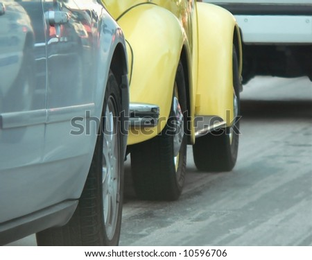Detail of stalled, bumper to bumper traffic which is a common aggravation around the world or appropriate with a message of fuel efficiency. Silver car behind yellow car behind white car on roadway - stock photo