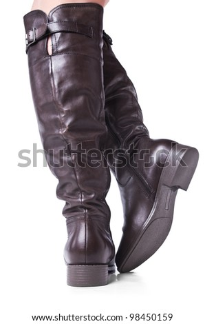 Detail of standing woman wearing brawn leather boots. Isolated on white background.