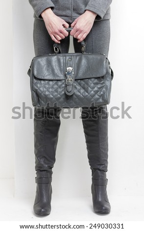 detail of standing woman wearing grey boots with a handbag - stock photo