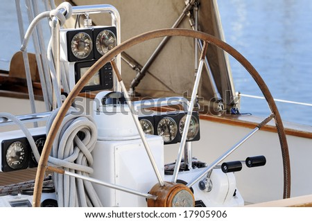 detail of steering wheel and navigation instruments of a sailboat - stock photo