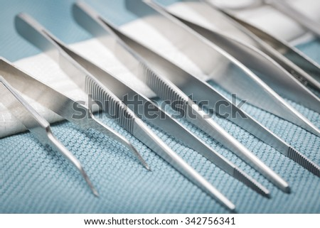 Detail of surgical instruments and tools on a tray covered with green cloth