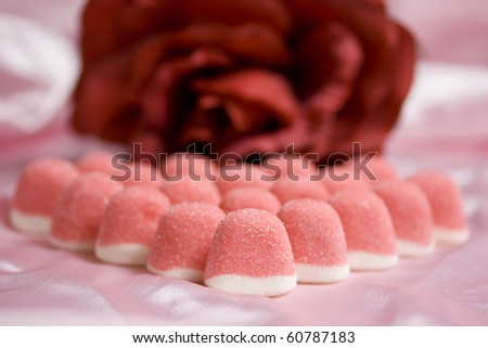 Detail of sweet pink jelly candies on pink satin - red rose in the background.