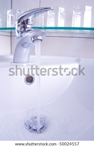 Detail of tap with running water and glasses in background. - stock photo