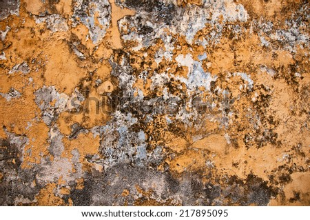 Detail of Texture of Cement Wall with Chipped Yellow Peeling Paint - stock photo