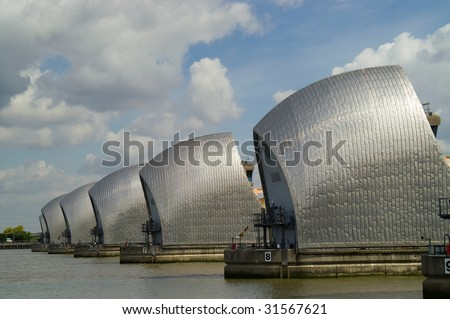Detail of Thames Barrier on river Thames, against blue sky with clouds