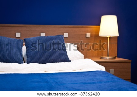 Detail of the bed and lamp in a blue hotel room - stock photo