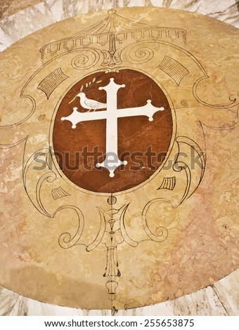 Detail of the Duome floor with a medallion representing a white cross and a dove with an olive branch - stock photo