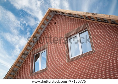 Detail of the facade of a brick house with a roof and windows - stock photo