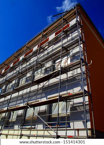 detail of the facade of a large building at the insulating walls with visible scaffolding all over the wall - stock photo