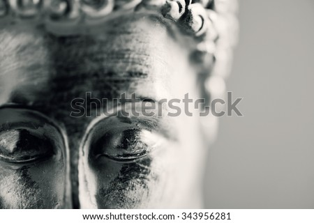 detail of the face of a representation of the buddha with his eyes closed in duotone - stock photo