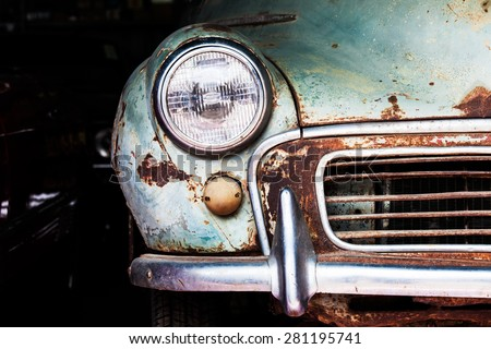 Detail of the front headlight of an old car in garage - stock photo