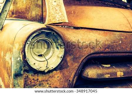 Detail of the front headlight of an rusty car in garage