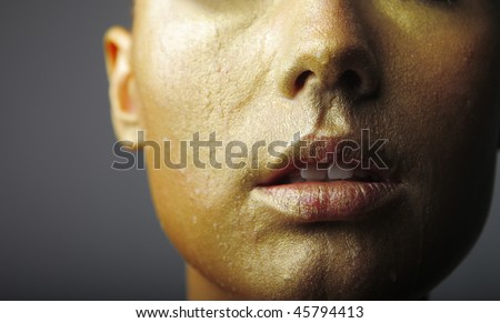 Detail of the gold colored visage of a beautiful woman - stock photo
