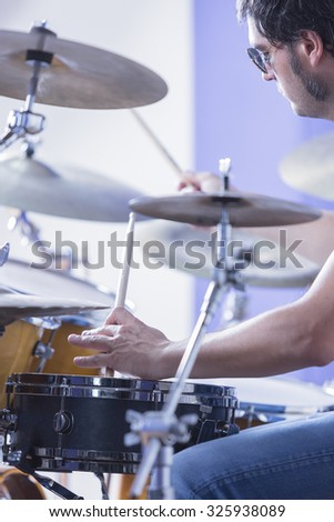 detail of the hand of a drummer that is holding drumsticks playing drums in a recording studio - focus on the left hand - stock photo