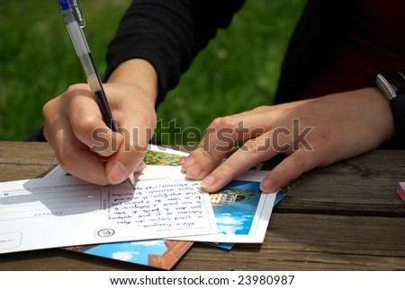 Detail of the hand of a lady writing a postcard. - stock photo