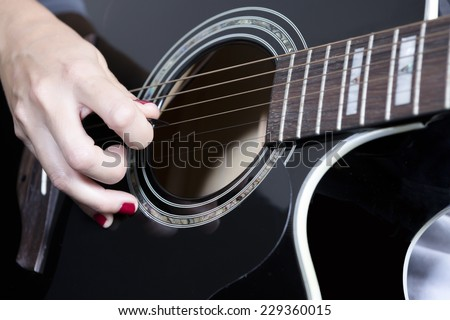 detail of the hand of a young woman holding a guitar pick near the rosette playing a black acoustic guitar - focus on the pick