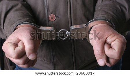 detail of the hands of a arrested man, with handcuffs