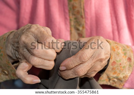 Detail of the hands of a senior person sewing