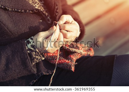 Detail of the hands of an elderly person crocheting outdoors