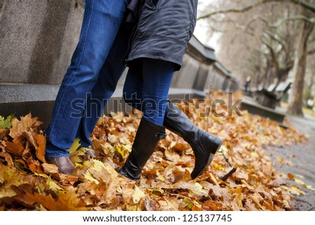 Detail of the legs of a couple kissing at the park in autumn - stock photo